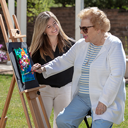 Art instructor with senior woman painting on easel outside