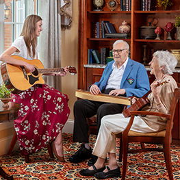 Music therapist playing guitar with two residents
