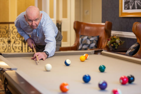 Male resident playing pool in the Billiard Room