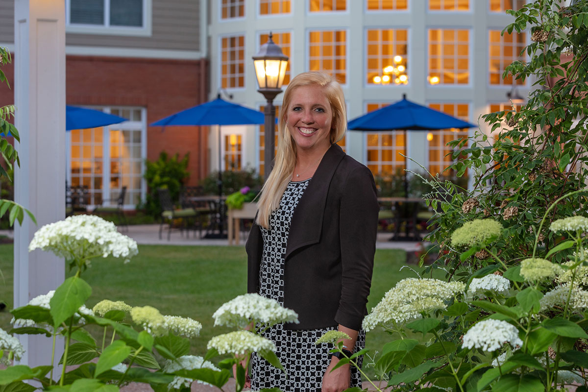 Executive Director, Laura Ritthamel, standing outside under the back patio pergola.