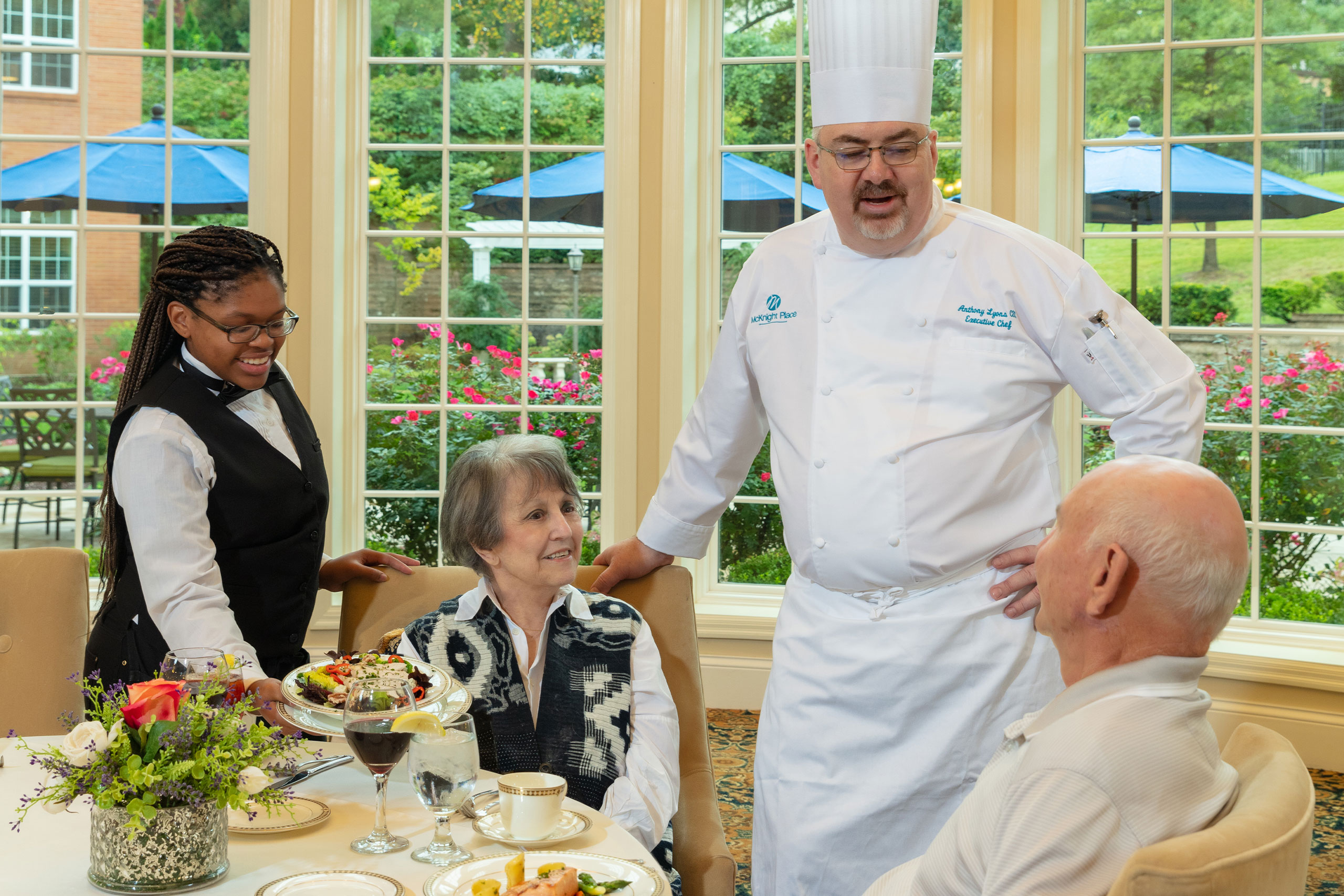 Executive Chef speaking with residents during meal.