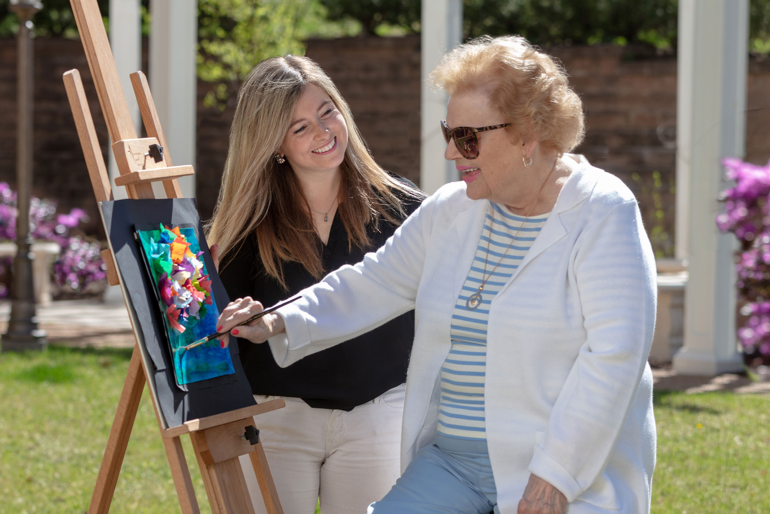Art Therapist and resident painting on easel in outdoor courtyard.