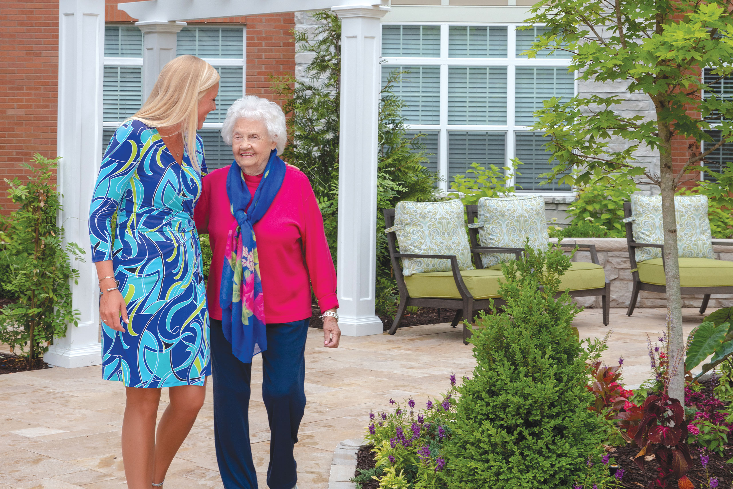 Assisted Living and Memory Care Executive Director and resident walking in outdoor gardens.