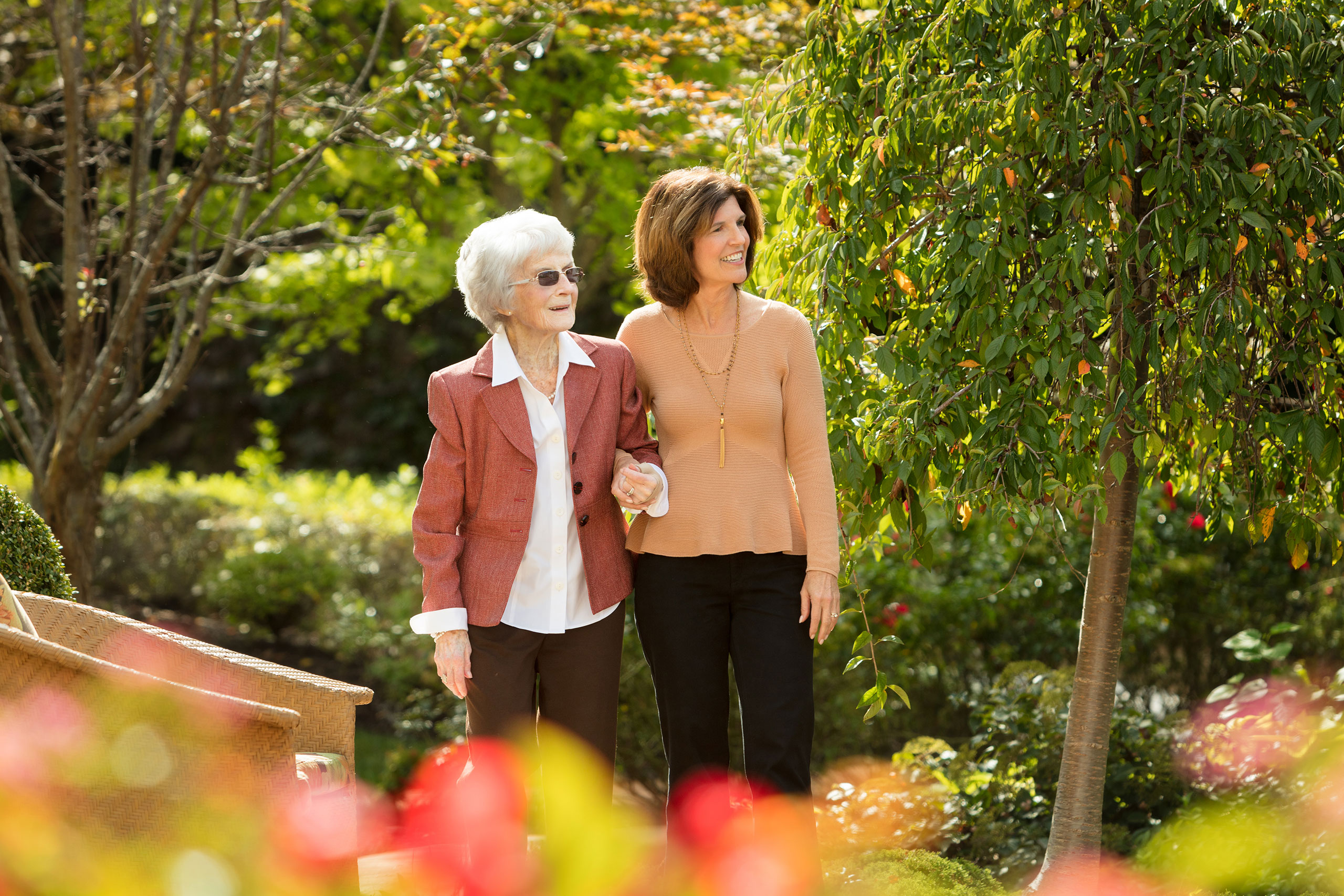 Daughter and resident walking through outdoor gardens.