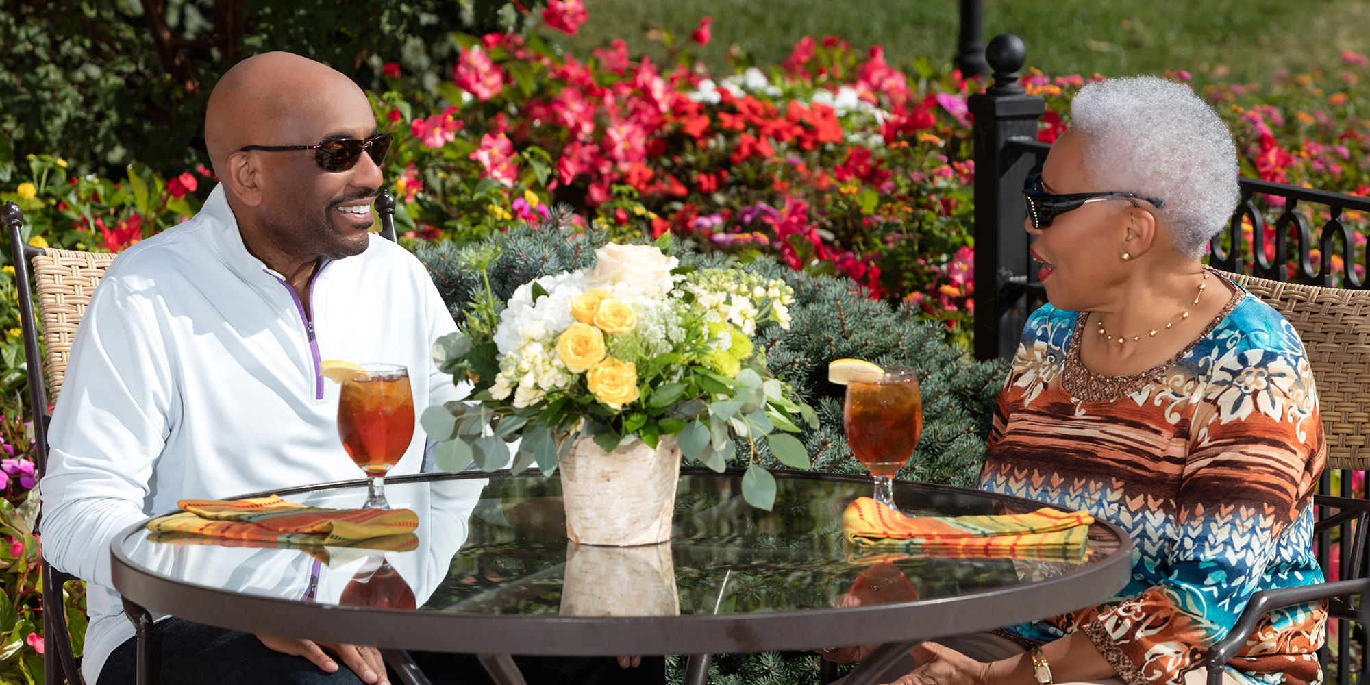 Couple enjoying iced tea on patio.