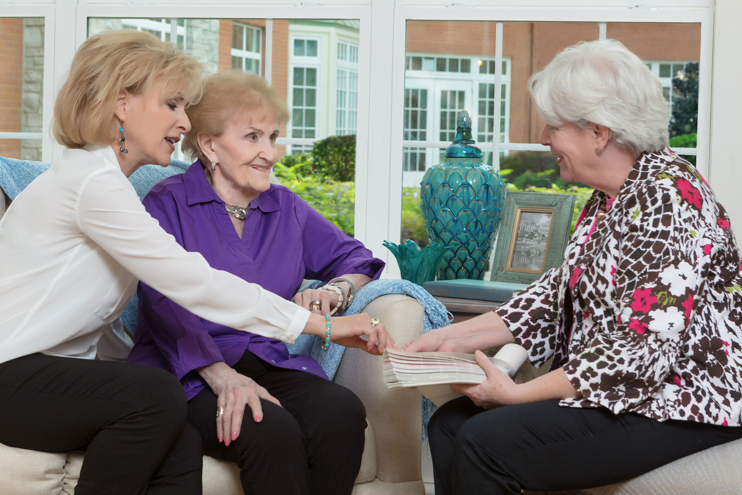 Move-in Coordinator reviewing interior design options with caregiving and resident.