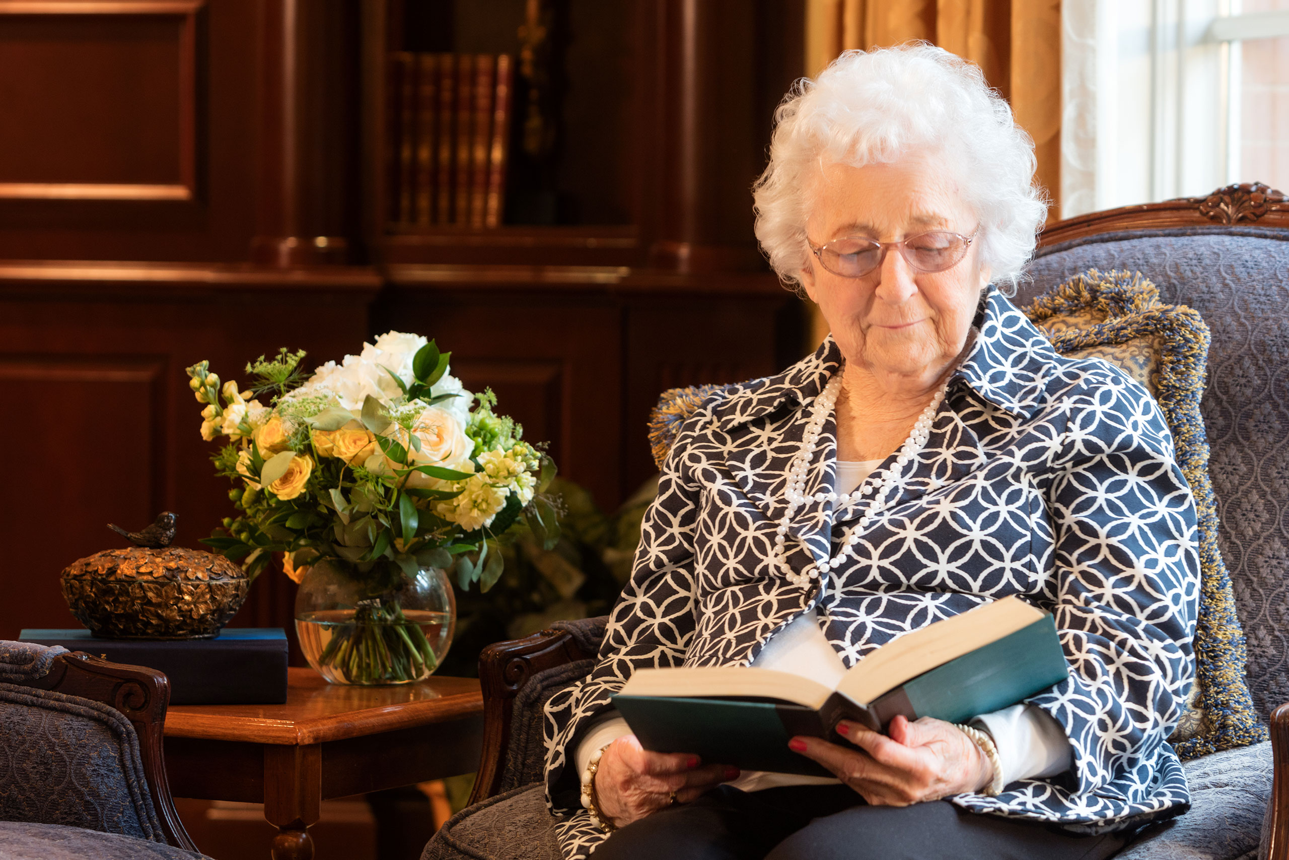 Female resident reading a book in the living room.