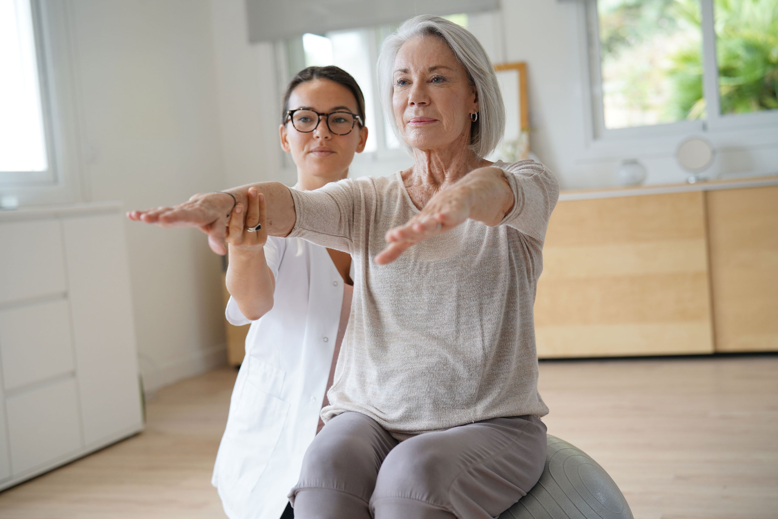 Senior woman exercising with her physiotherapist and swiss ball.