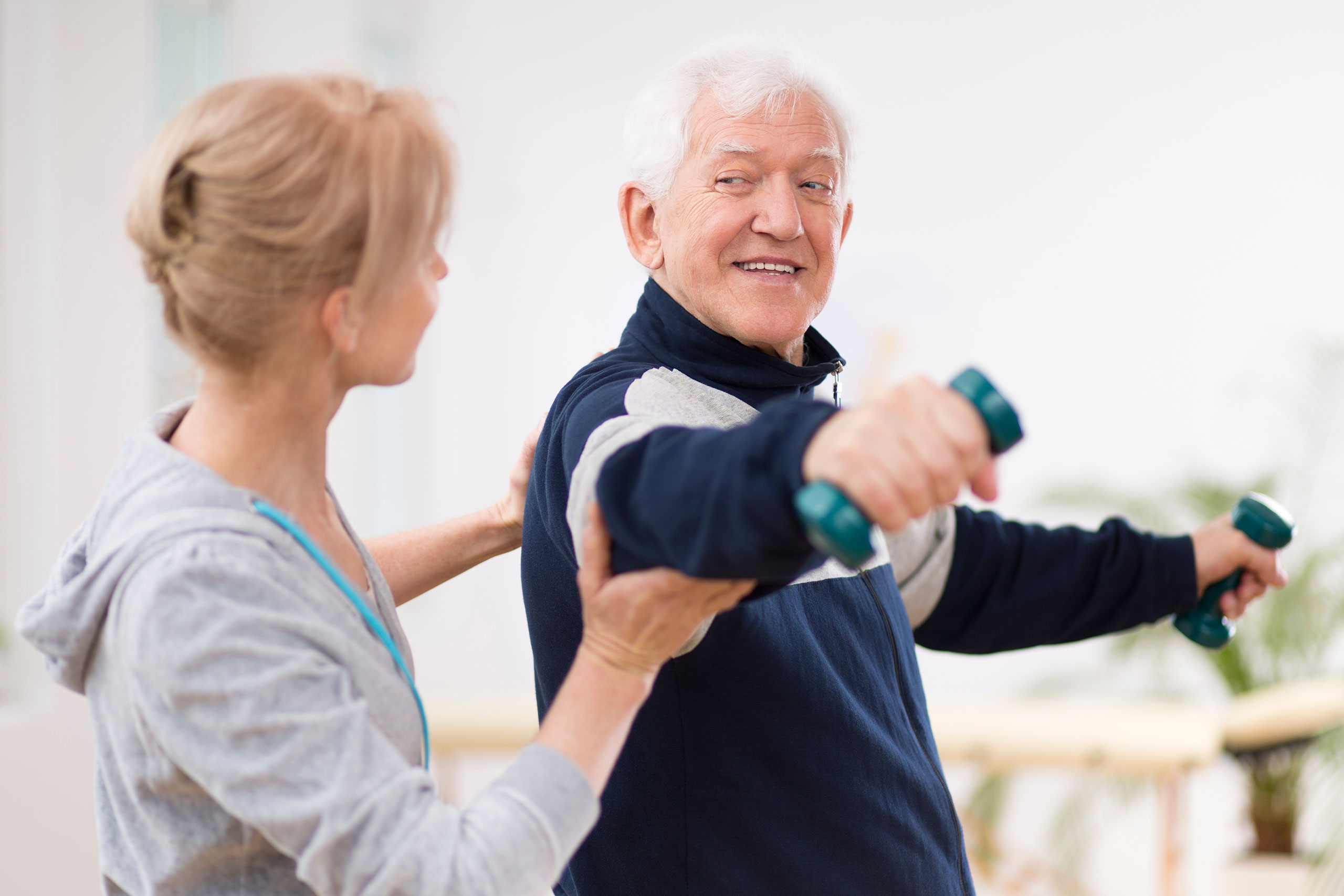 Senior man after stroke at nursing home exercising with professional physiotherapist.