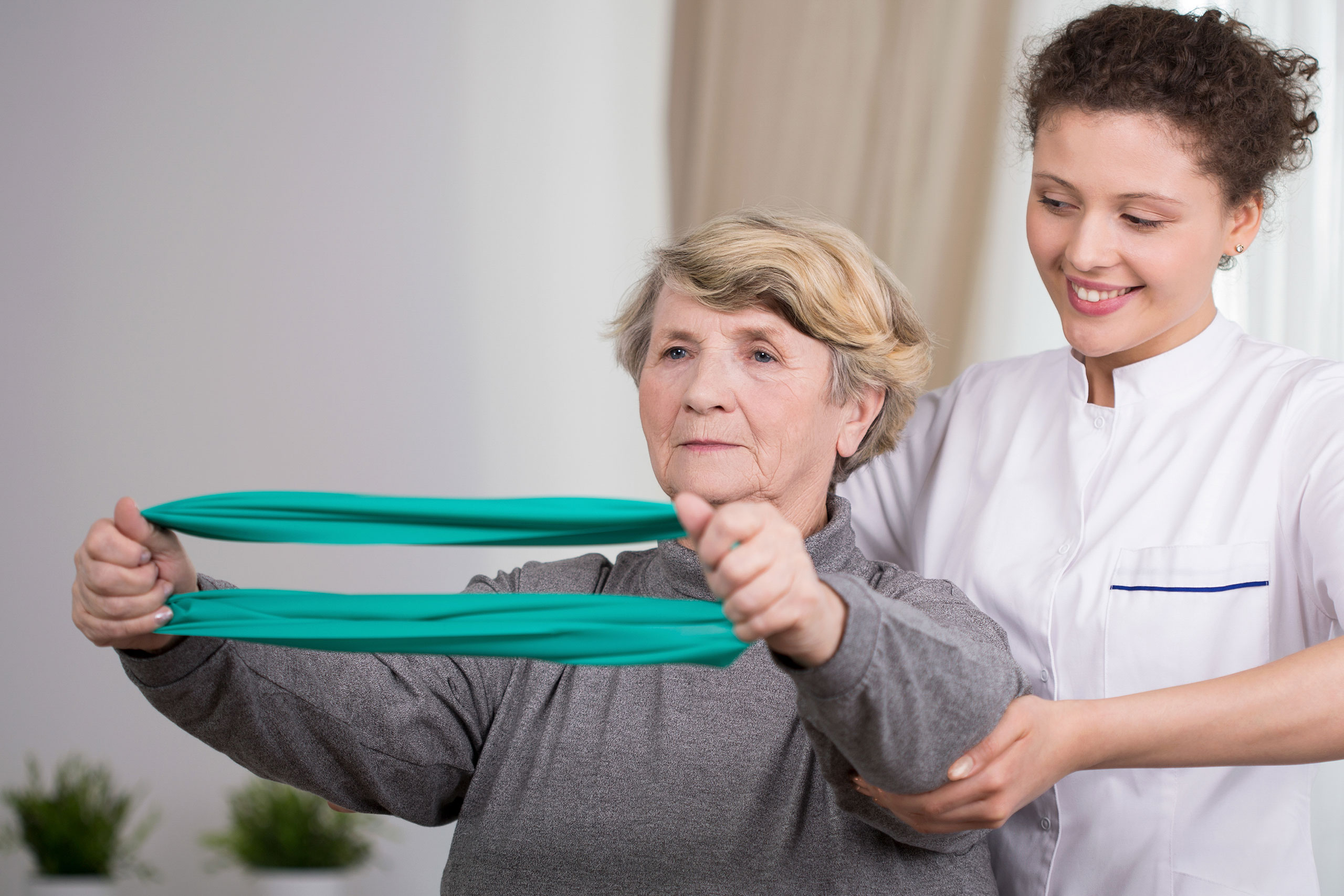 Elderly active woman exercising with young physiotherapist.