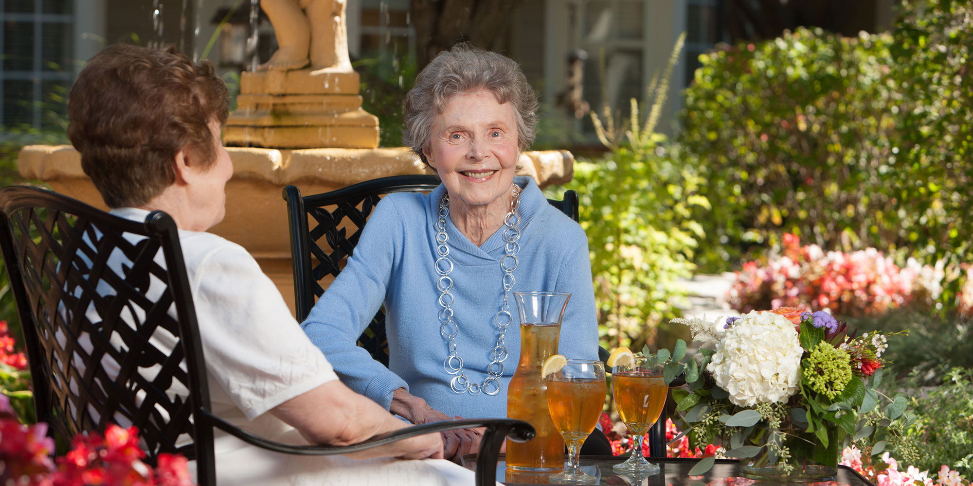 Two women enjoying iced tea on the outdoor courtyard.