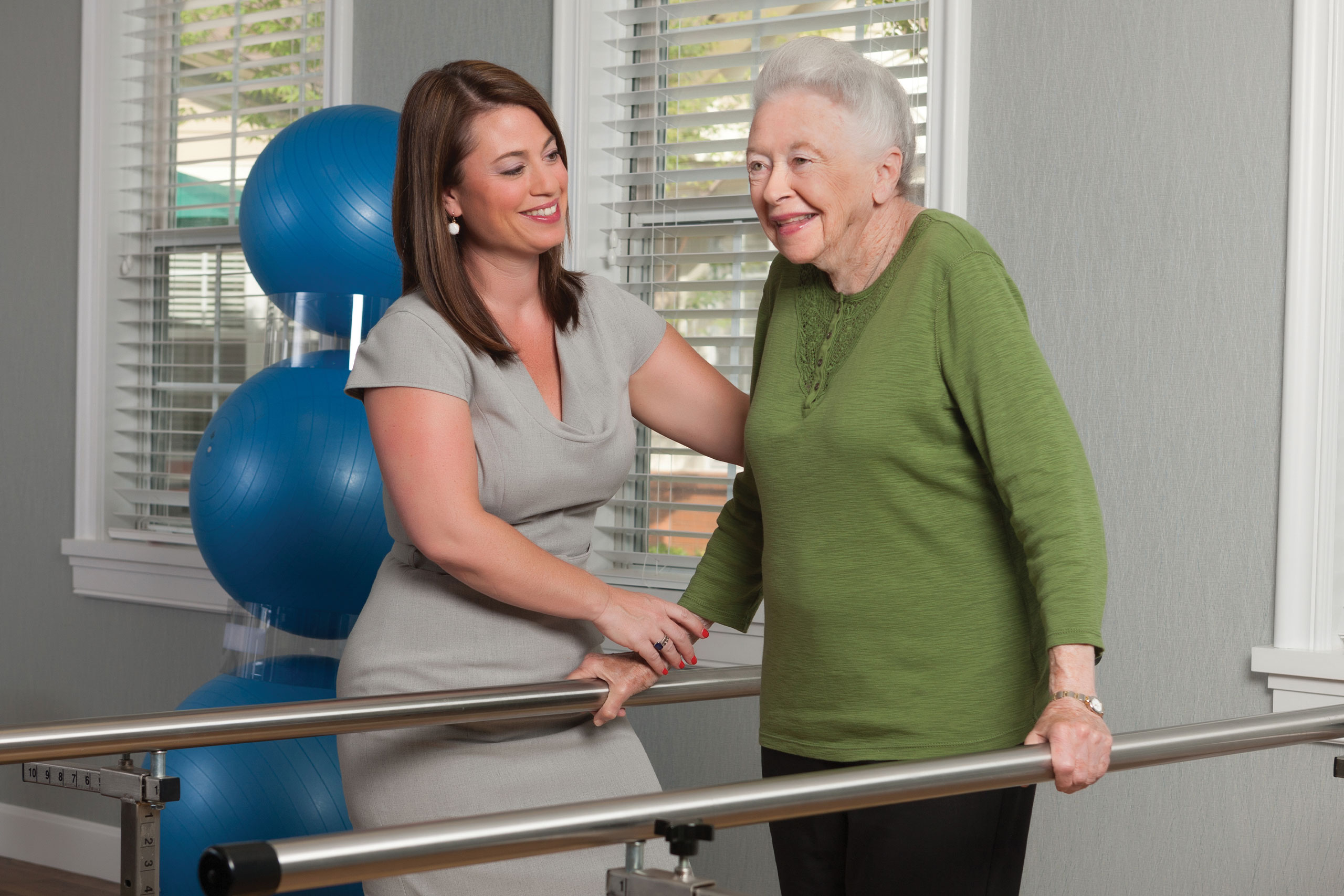 Therapist working on rehabilitation bar exercises with resident.