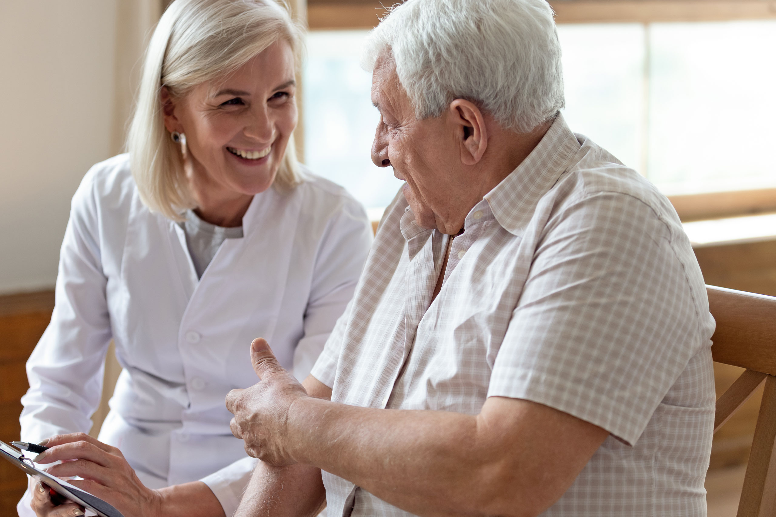 Elderly man and therapist holding clipboard writing personal information having pleasant warm conversation.