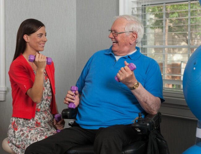 Therapist working on a dumbbell exercise with resident.