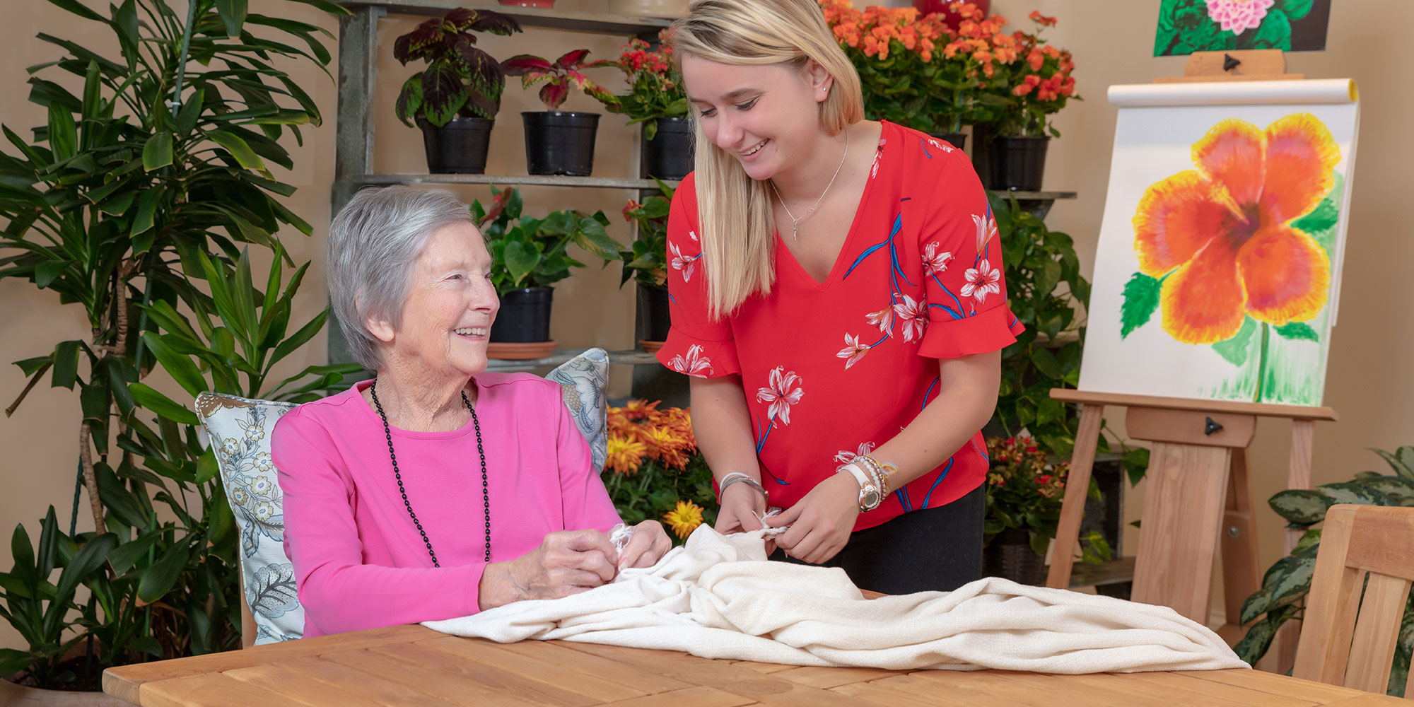 2 women working with a quilt and smiling