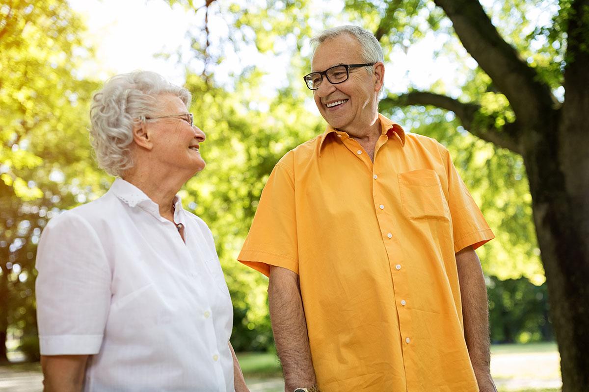 Older happy couple walking through park.