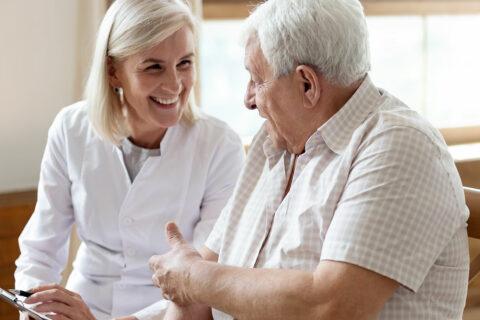 Caretaker and elderly man having a conversation.